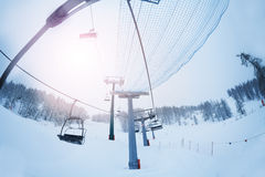 Aerial ropeway with empty chairlifts at foggy day Stock Photo