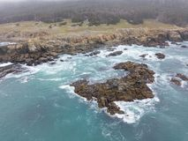 Aerial of Rugged Northern California Coastline. The cold waters of the Pacific Ocean wash against the rocky Northern California coastline in Sonoma. This royalty free stock photography