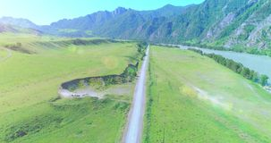 Aerial rural mountain road and meadow at sunny summer morning. Asphalt highway and river. Aerial UHD 4K: mid-air flight over rural mountain road and meadow at stock footage
