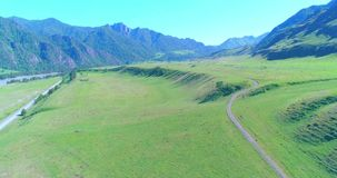 Aerial rural mountain road and meadow at sunny summer morning. Asphalt highway and river. Aerial UHD 4K: mid-air flight over rural mountain road and meadow at stock video