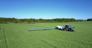 Tractor with trailer tank sprinkles soybean field with chemicals
