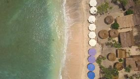 Aerial: Sandy Beach with Umbrellas and Lounge Beds at Paradise Tropical Island. Nusa Penida, Indonesia. 4K Seaside Top. View Background stock video footage