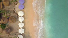 Aerial: Sandy Beach with Umbrellas and Lounge Beds at Paradise Tropical Island. Nusa Penida, Indonesia. 4K Seaside Top. View Background stock video