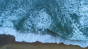 Aerial of the sandy beach that is washed by turquoise sea waves in Sri Lanka. Lright turquoise sea waves foam and wash the sandy beach at the resort in Sri Lanka stock footage