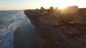Aerial scene with beach drones. Zoom in The camera moves forward of the beach with people in the sea and sunset in the background.