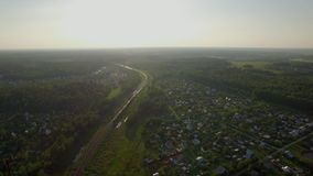 Aerial scene with countryside and moving train, Russia. Aerial - Train running through the countryside with summer houses among the green forests. Summer scene stock video footage