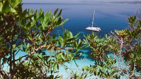 Aerial scene from the rocky coast to a catamaran anchored in a bay of the greek Islands. Idyllic island with transparent. Turquoise water. Paradisiac landscape stock video