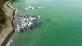Aerial sea. Birds fly over the sea. The waves beat on the reefs and shore stock video footage