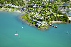 Aerial of seaside town. Aerial of Airlie Beach in Queensland Australia. Looking down from above at a seaside town surrounded by boats and blue ocean Stock Images