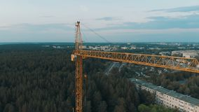Aerial shoot bird view of yellow tower building crane fly around construction site building apartments real estate. Background beautiful view stock footage