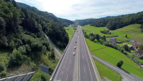 Aerial shoot of a traffic on a highway road. Aerial slow motion shoot of a traffic full of cars and trucks on a highway road in a valley stock video footage