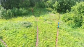 Aerial shoot of trail running athletes. Crossing off road terrain at sunny day stock video footage