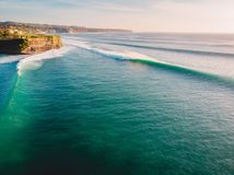 Aerial shooting of big waves at sunset. Biggest ocean waves in Bali and coastline Royalty Free Stock Images