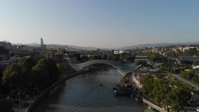 Aerial shooting of the city center of Tbilisi in Georgia. Peace Bridge. The camera flies a radius around the bridge stock video footage