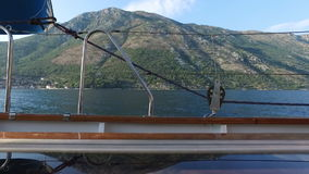 Aerial shooting from the deck of a yacht in the sea near the mountains.  stock footage