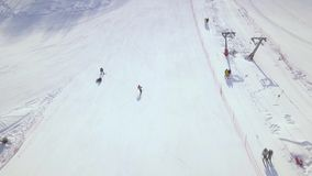 Aerial shooting from flying drone people skiing and snowboarding on snow slope in winter ski resort. Ski elevator on. Snow mountain. Winter activity on ski stock video