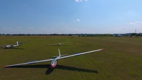 Three sports gliders plane lie on the wing in the field, aerial shooting. Aerial shooting of gliders in green field stock video