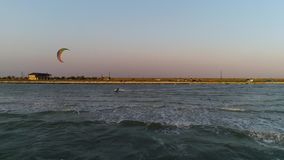 A man in a diving suit is engaged in kitesurfing on the coast. Aerial shooting, a lone kiter sails past a beach camp with a house stock footage
