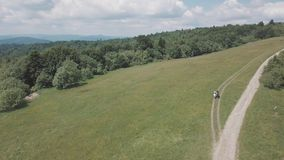 Aerial shooting. Look from above at people riding horses on the mountains.  stock footage