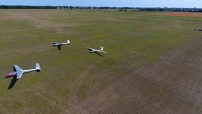 Aerial shooting of three glider planes in an even green field in a sunny day. Three shiny gliders lie on the wing in the field stock footage