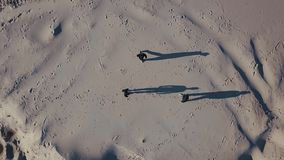 Aerial shooting. Three mens converge in the desert. The sun throws shadows in the sand. Top view