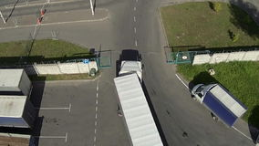 Aerial shooting: The truck drives through a sliding gate. The truck faces iron automatic gate, they open, the truck passes, aerial shooting stock video footage