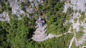 Aerial shot of amazing house inside cliff in italian mountains in sunny summer day, view from birds eye stock video
