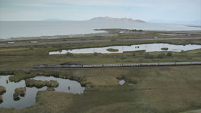 Aerial shot of Amtrak train and Great Salt Lake stock video