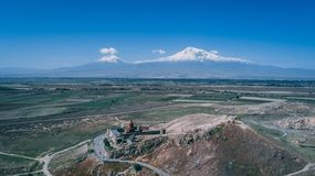 Aerial shot of an Armenian church on a hill with mountain Ararat and clear blue sky royalty free stock photo