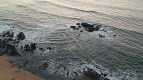Aerial shot on beach just after sunrise in Portugal looking over Atlantic ocean with waves crashing. On rocks while flying straight down stock video