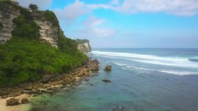 Aerial shot on the beach beside the Uluwatu cliff Bali stock footage