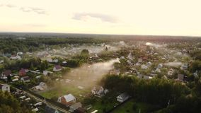 Aerial shot of beautiful countryside village in the morning sunlight, with mist floating on the farm land field. Cooking stock video footage