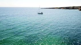 Aerial Top View of a sailboat in blue water stock video