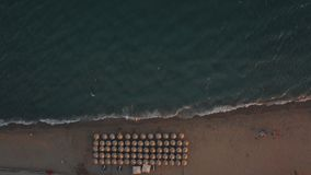 Aerial shot of blue sea and sunbeds under umbrellas at the beach. Distant aerial view of sea and shore with rows of sunbeds, straw umbrellas and few people at stock video