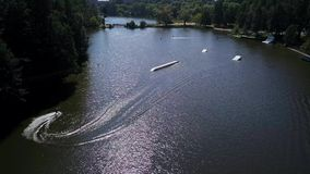 Aerial shot of a cableway in a lake with a wakeboarder stock video