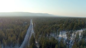 Aerial shot camera rising above winter road from close up to whole landscape to horizon. Background snowy north forest. Aerial shot rising above winter road from stock video