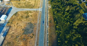 Aerial shot. Car driving on the road. Forest. Railway. Train. Sunny stock footage