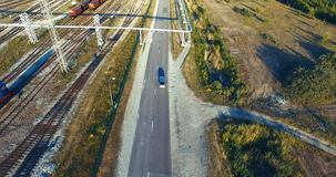 Aerial shot. Car driving on the road. Forest. Railway. Train. Sunny. Car driving on the road, near the forest, railway, train. Day is sunny stock video footage
