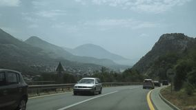 Aerial shot of car passing on the highway to the mountains. Natural travel speed stock footage