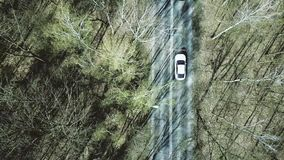 Aerial shot of car road in the forest on a spring day, top view. 4K video. Aerial shot of car road in the forest on a spring day, top view. 4K clip stock footage