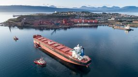 Aerial shot of a cargo ship approaching port terminal with help of towing ship. Narvik, Norway royalty free stock photos