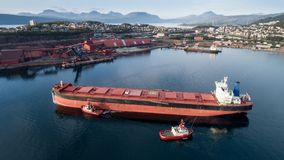 Aerial shot of a cargo ship approaching port terminal with help of towing ship Stock Images