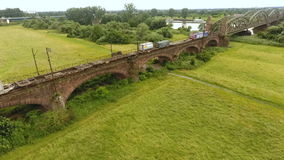 Aerial shot of a cargo train. Hochheim, Germany - June 22, 2016: An aerial shot of a cargo train of German railroad company DB passing a train bridge between stock video footage