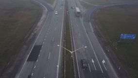 Aerial shot. Cars driving by the road. Transport interchange. Cars ride under and above the bridge. Thick fog. Aerial shot. Cars driving by the road. Transport stock video footage