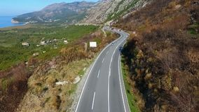 Aerial shot of cars passing on the highway to the mountains.  stock video footage