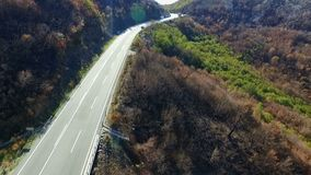 Aerial shot of cars passing on the highway to the mountains.  stock footage