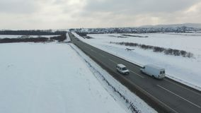 Aerial shot of cars and trucks driving on a road on winter cloudy day. Drone moves along road stock video