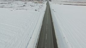 Aerial shot of cars and trucks driving on a road on winter sunny day. Drone moves along road stock video footage