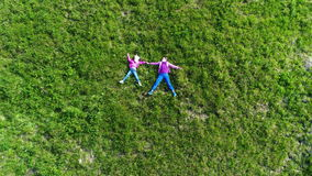 Aerial shot of children at green grass. View of family walking the village Yablunytsia in Carpatian mountains, drone camera stock video