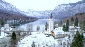 Aerial shot of church and bridge at Bohinj lake. In winter stock video footage